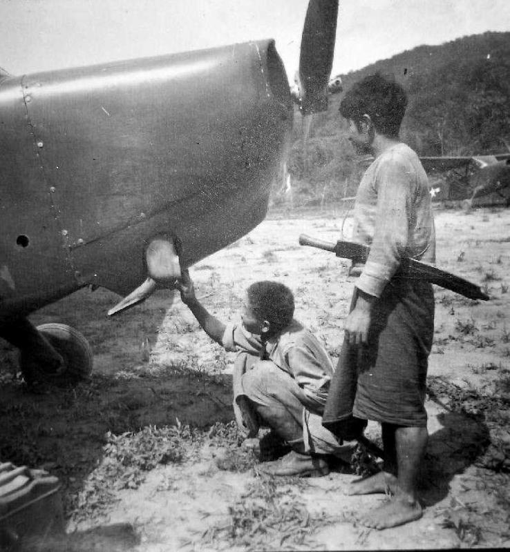 Two boys in northeast India have a look at an American observation plane