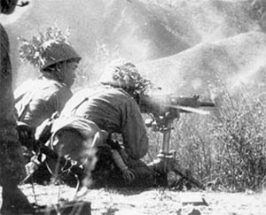 Japanese troops firing heavy machine gun, 1942